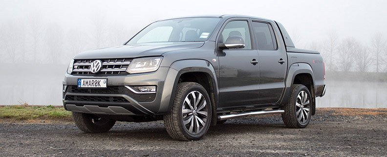 Grey Amarok parked on waters edge on gravel road