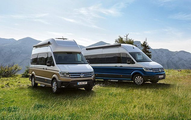 Two Volkswagen Grand California Campervans on grassy mountaintop.