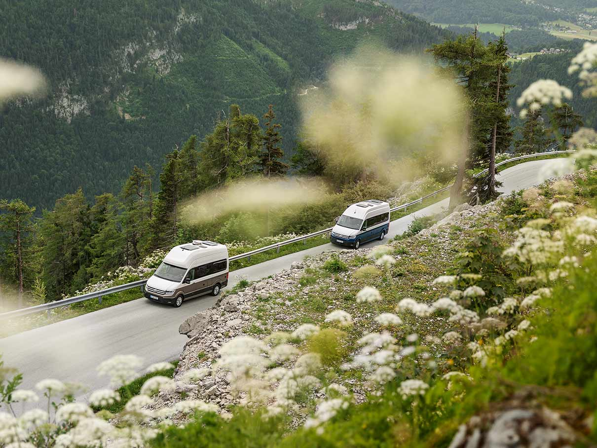 Two Volkswagen Grand California campervans driving through a mountain road.