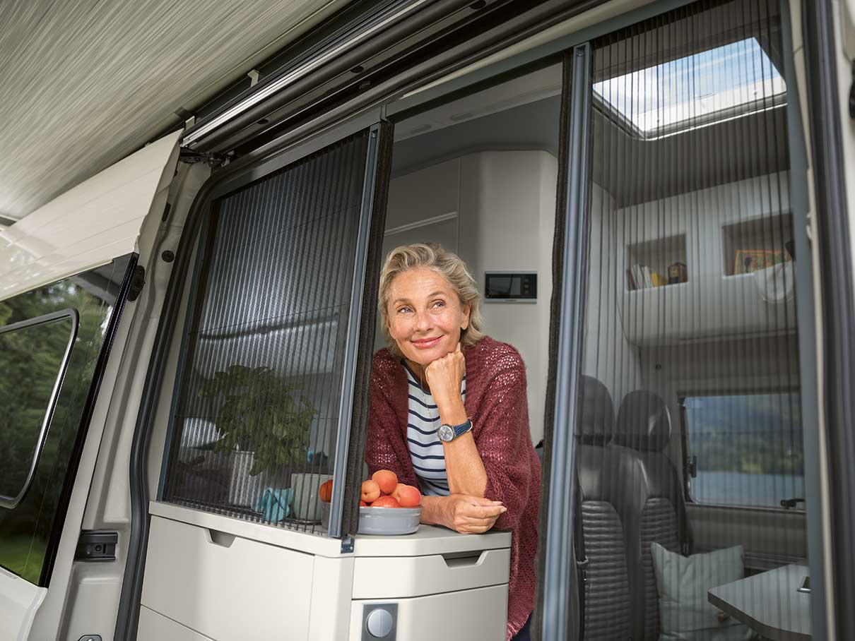 Woman looking out from her Volkswagen Grand California open door with screen.