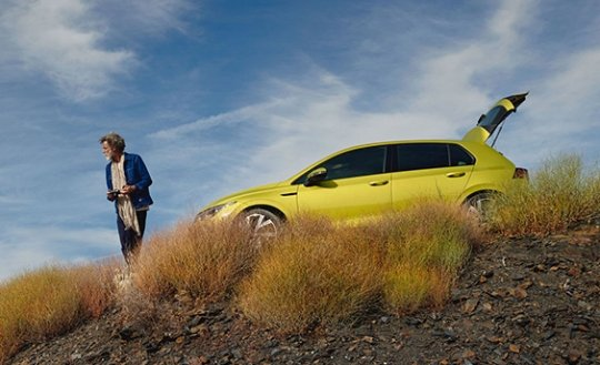 Yellow Volkswagen Golf 8 parked on a hilltop next to an older man who is holding a remote.