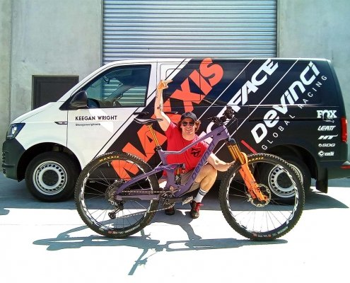 Pro mountain biker Keegan Wright poses with fist up in front of new Volkswagen Crafter and behind his mountain bike.