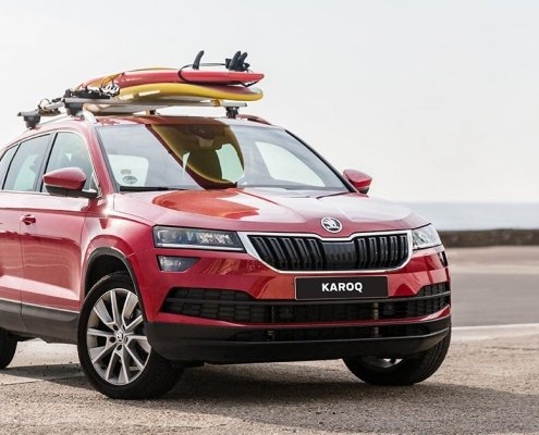 Red SKODA Karoq SUV on a beach with surfboards on top.