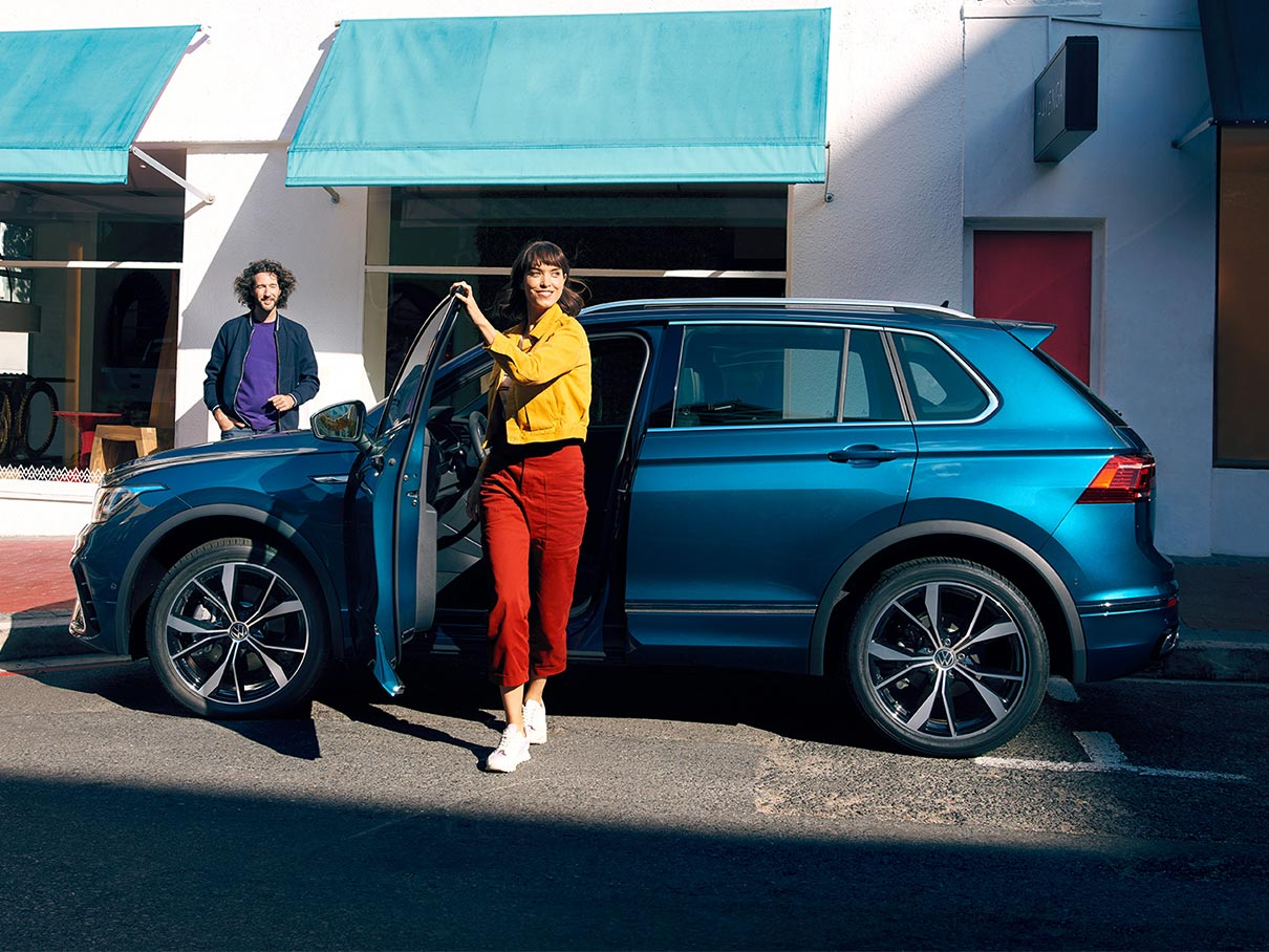 Blue Volkswagen Tiguan SUV with woman stepping out of the driver's seat on a city road.