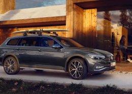 Volkswagen Passat Alltrack wagon parked in front of a modern wooden modular home.