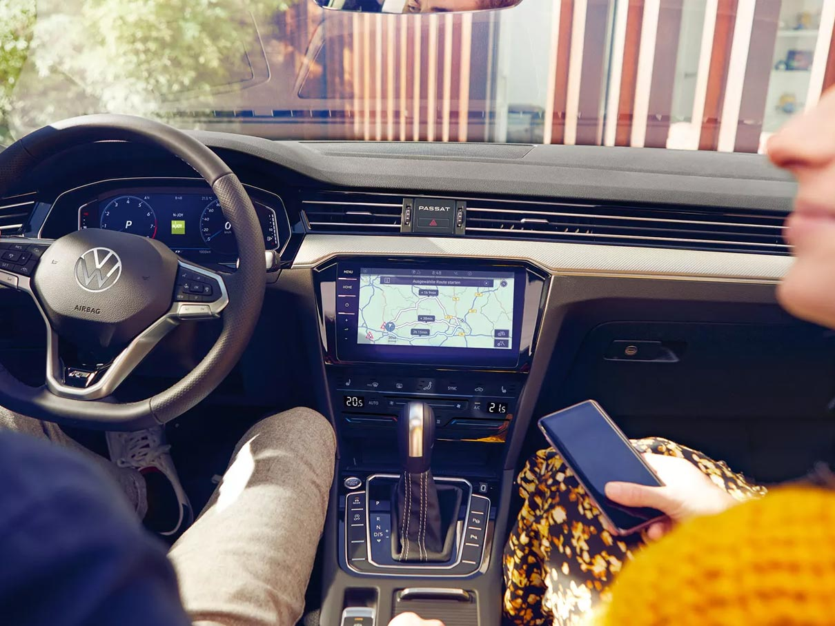 Man and woman sitting in front seats of a Volkswagen Passat Alltrack looking at their touchscreen.