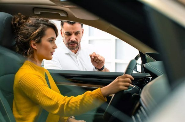 Woman driving a car with a man giving her instructions from outside.